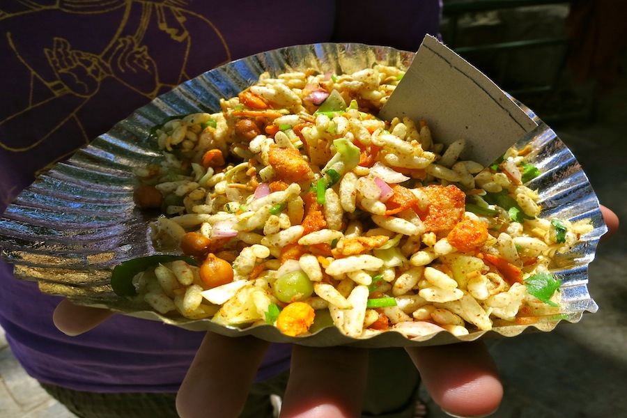 Bhelpuri is street food in India and Nepal. The men and women who sell it mix it by hand (literally with their fingers)  in a little plastic bucket and serve it to you in newspaper.