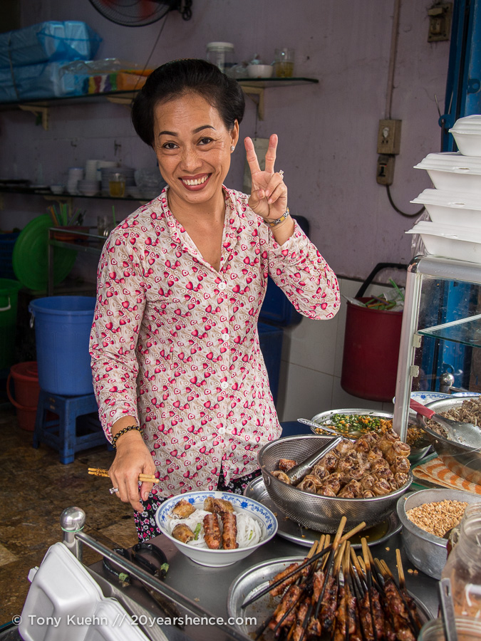 Smiling Vietnamese woman serves food