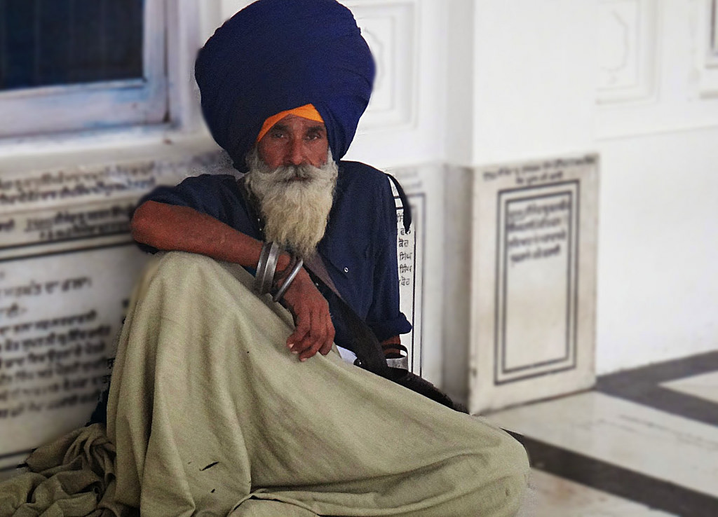 One of the many pilgrims sitting at Harmandir Sahib (or the Golden Temple) Amritsar. A true Sikh is supposed to carry 5 items all the time: Kesh: long hair, never cut and hidden under the turban Kanga: a wooden comb Kara: a massive metal bracelet that symbolizes the eternity and connection to God Katchera: specially tailored plain cotton undergarments Kirpan: an iron dagger or a full length curved sword.