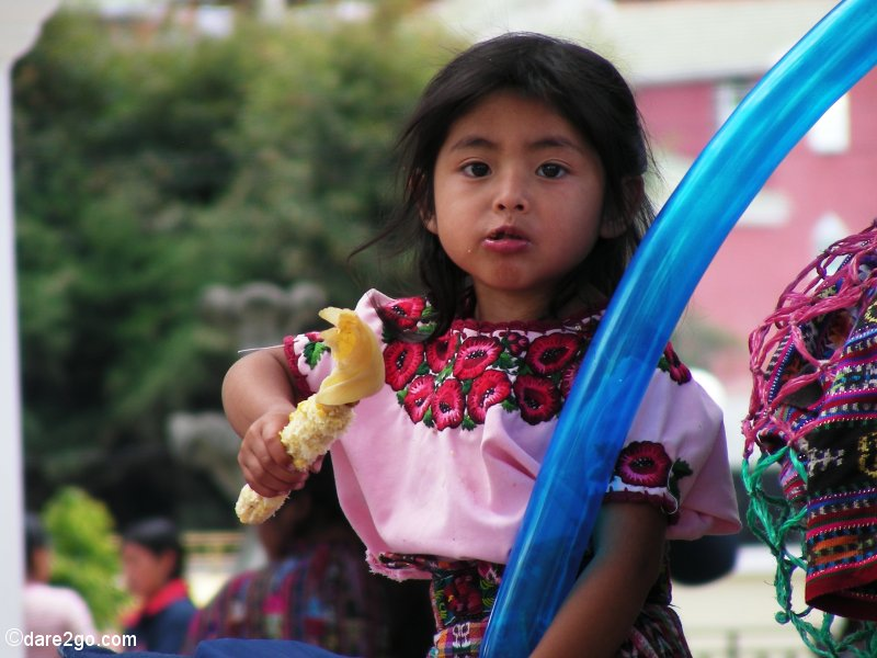 Market days in Guatemala (and other countries) are often a real social event for the whole family. This little girl in Solola (near Lago Atitlan) was thrilled by the small treads she had received: a buttered corn cob and a small blue balloon.