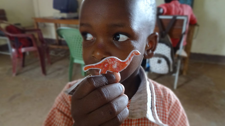 This is one of our students in Uganda. He refused to stay still so I could take his photo properly, but he really wanted to show me his prized dinosaur sticker. He's been keeping it in his pocket for a very long time!