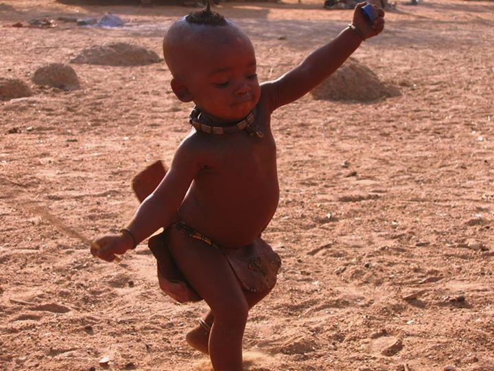 We were visiting a Himba village in Namibia and learning from the women who still maintain much of their traditional, semi-nomadic lifestyle. At some point I turned and saw this young boy dancing along with such joy waving his bottle cap and piece of straw.The photo is far from perfect, but it remains one of our favorites. Looking at him, you can't help but smile.